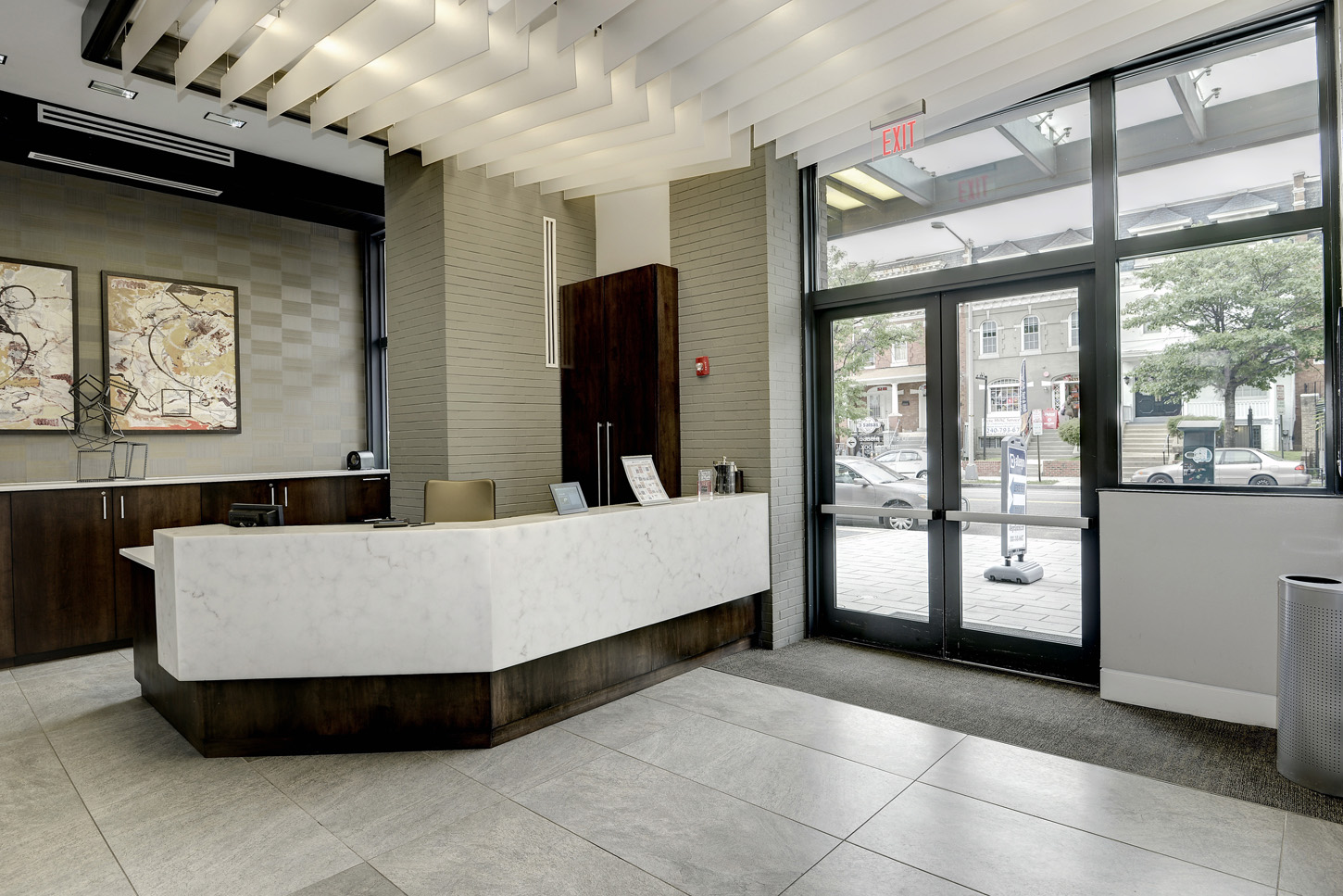 Lobby entrance with large marble concierge desk and abstract art behind it