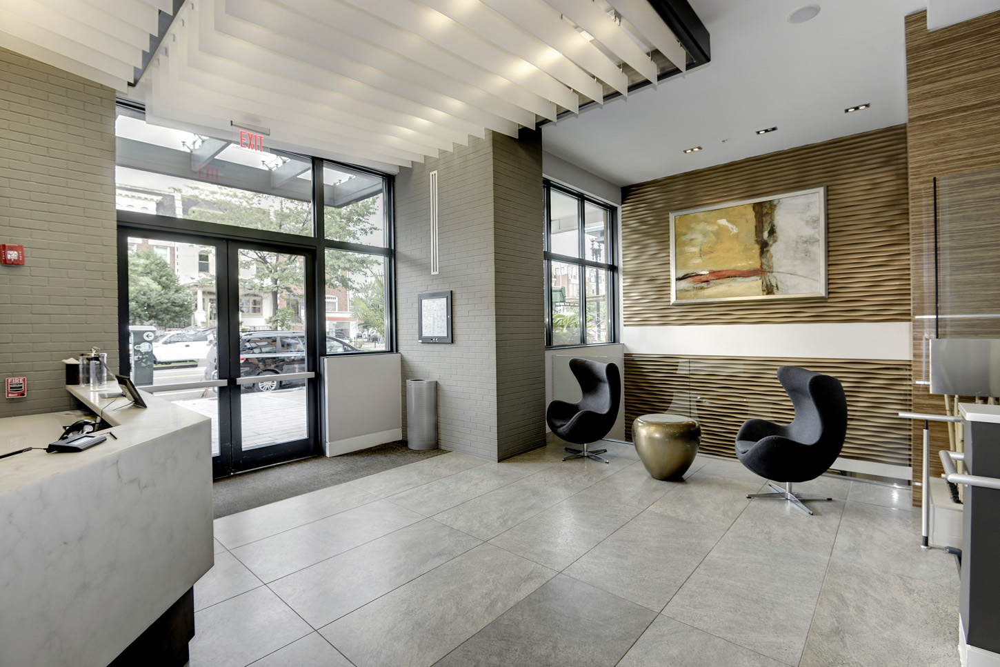 Interior of building entrance with view of modern lobby seating and large abstract art on wood wave wallcovering