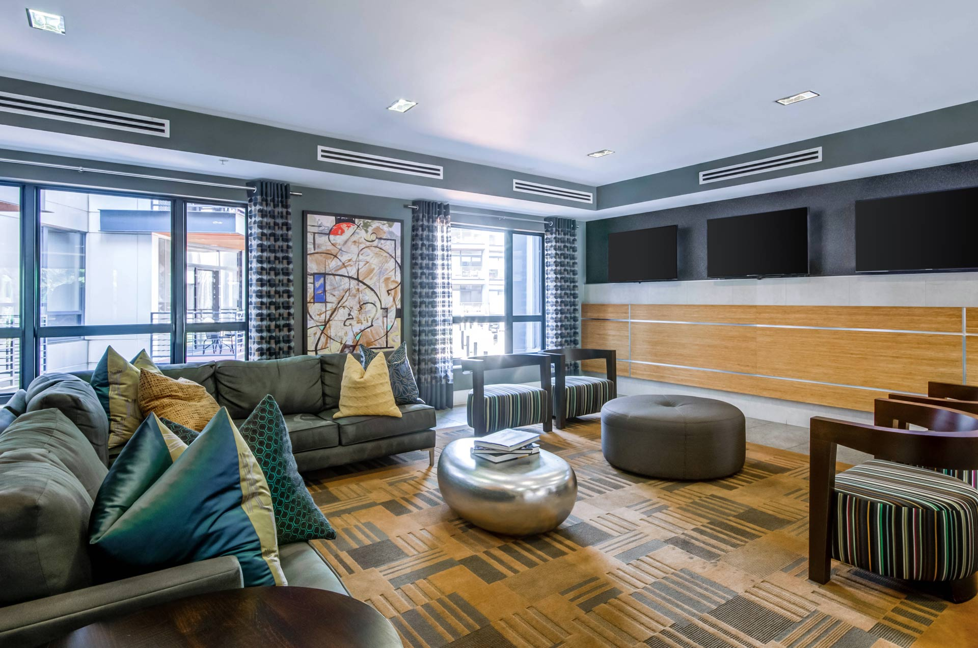Entry lounge area with comfortable sofas, large pillows, and multiple TVs over a graphic rug, with bright light filtering in from the windows behind