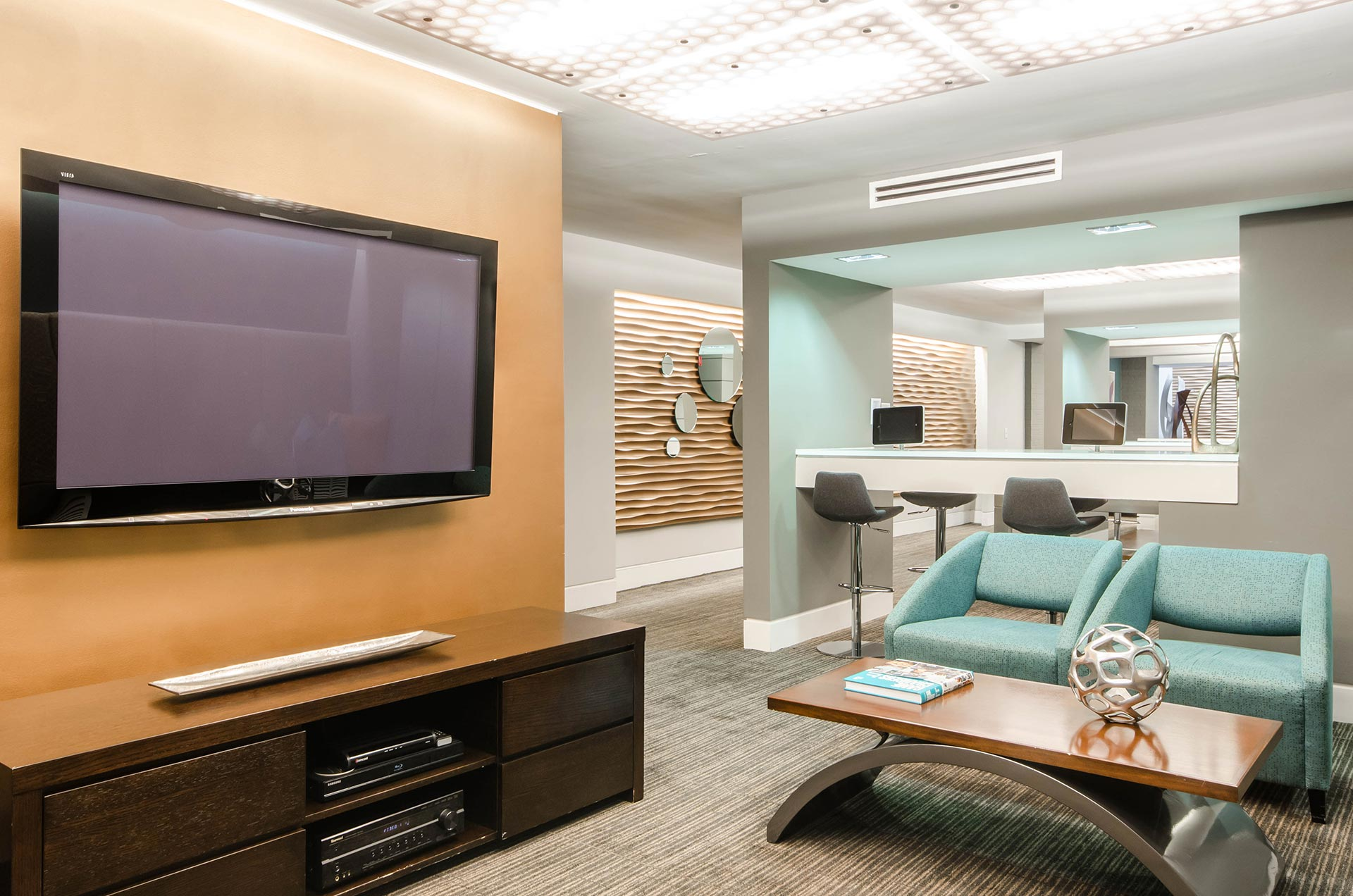 Brightly lit entertainment center with large TV and armchairs