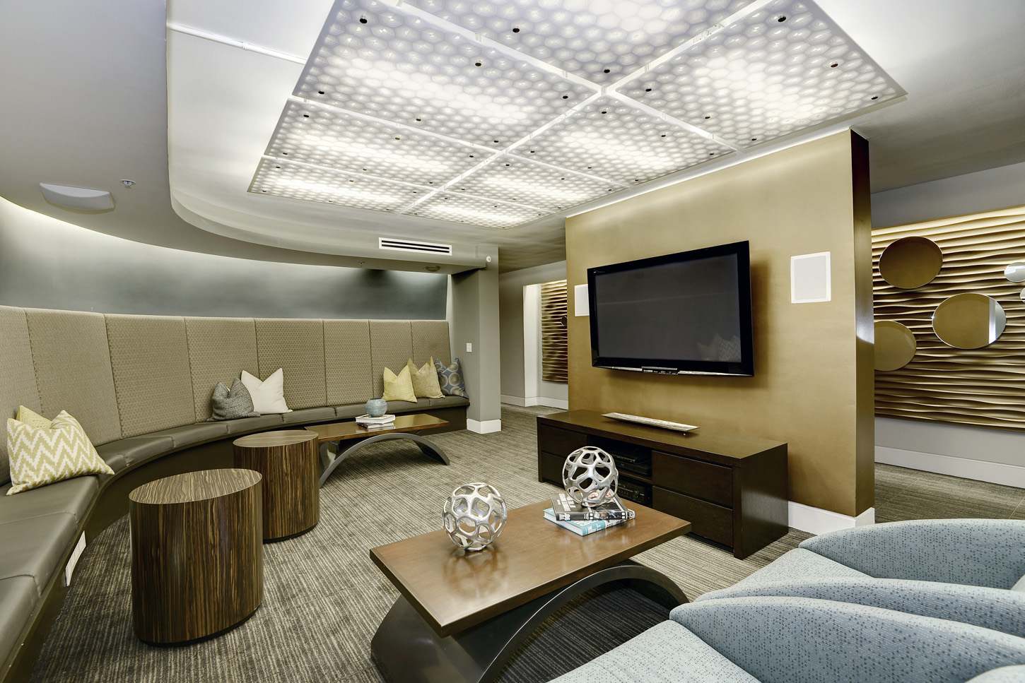 Entertainment center lounge with banquette seating and armchairs, with open hallway beyond