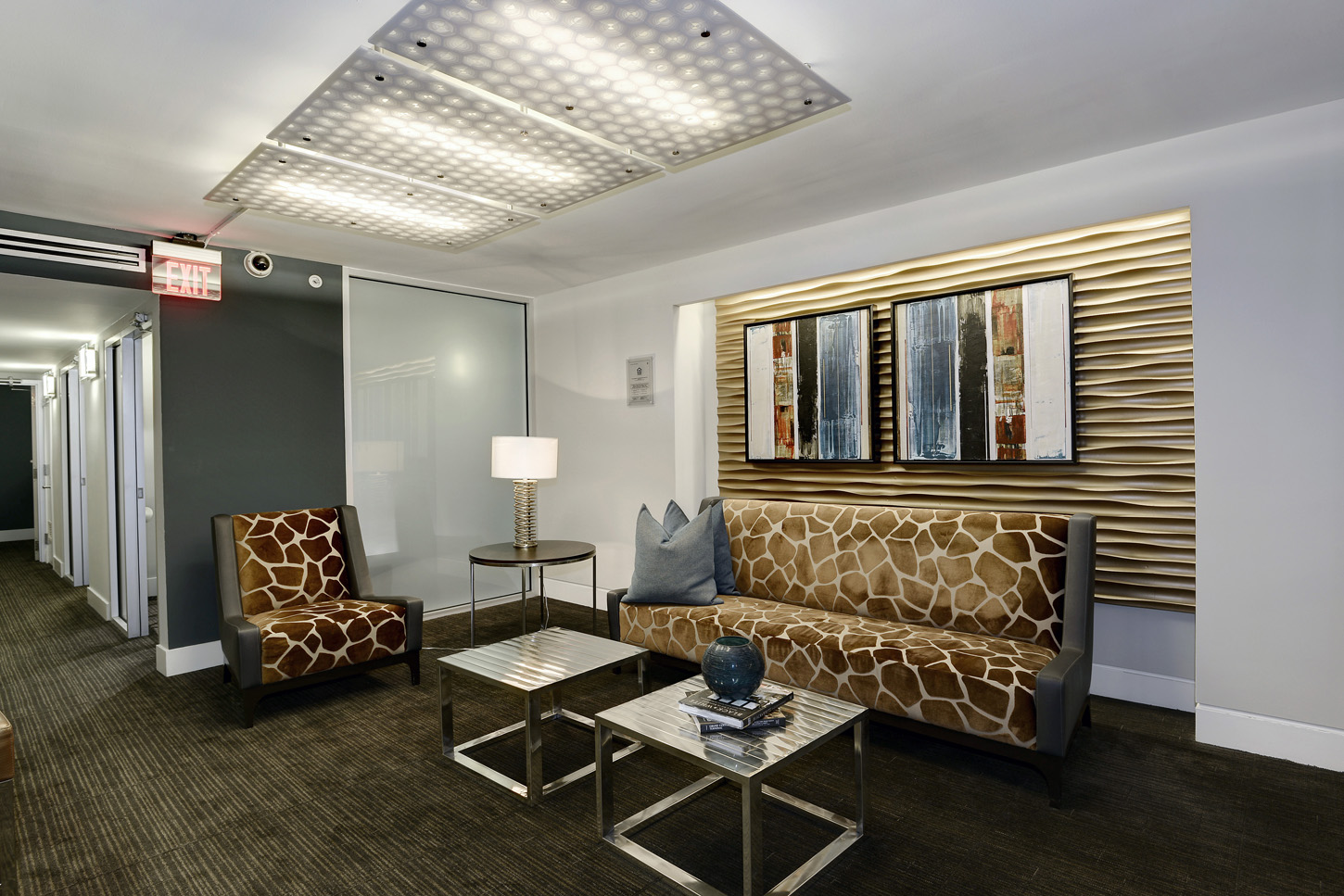 Clubroom hallway with graphic patterned sofa and chair, and entry to conference rooms to the left