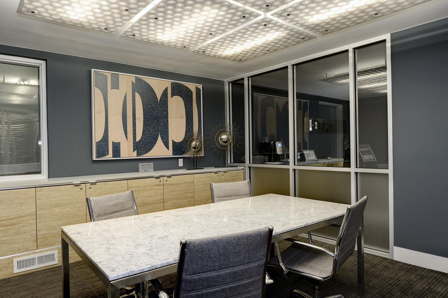 Brightly lit conferencing room with large table and shelving for catering or storage