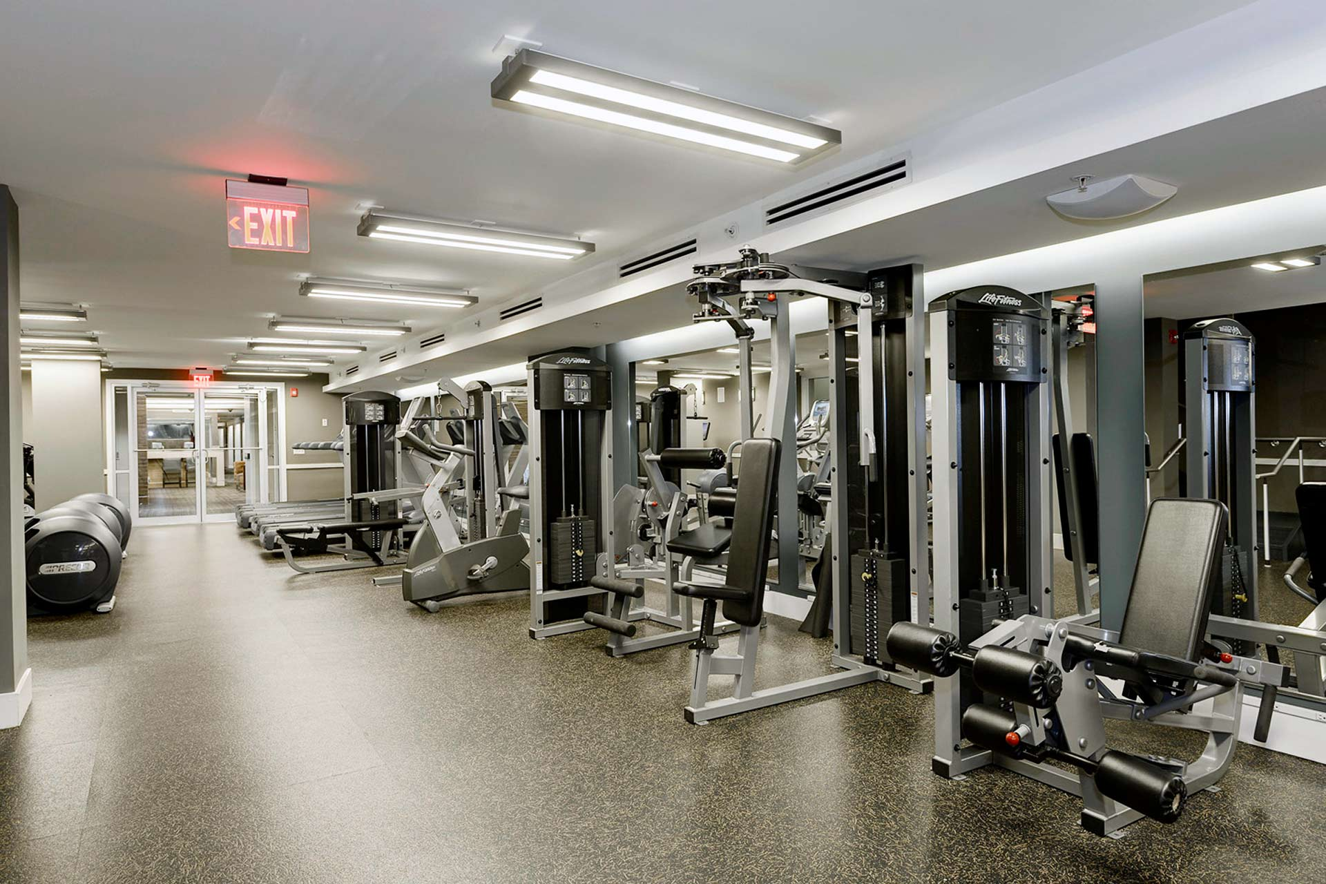 Large fitness room with impact absorbent flooring and strength training equipment along the right, mirrored wall