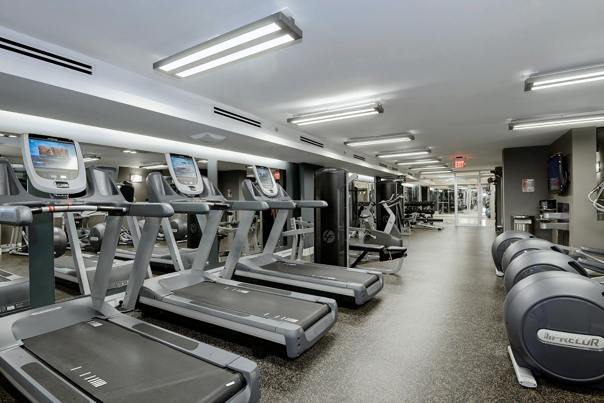 Large fitness room with impact absorbent flooring and cardio equipment along the left, mirrored wall