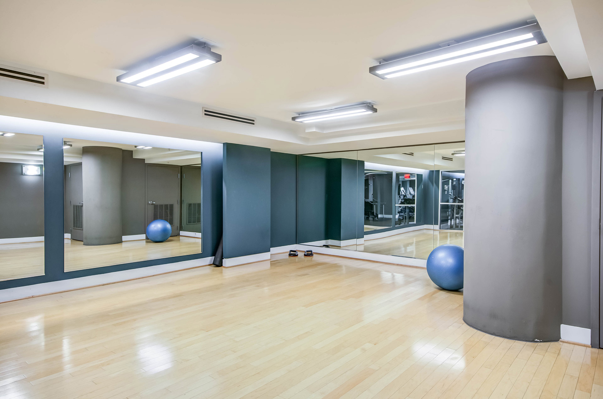 Clean and bright yoga and stretch studio with light wood flooring, mirrored walls and basic equipment stored to the right