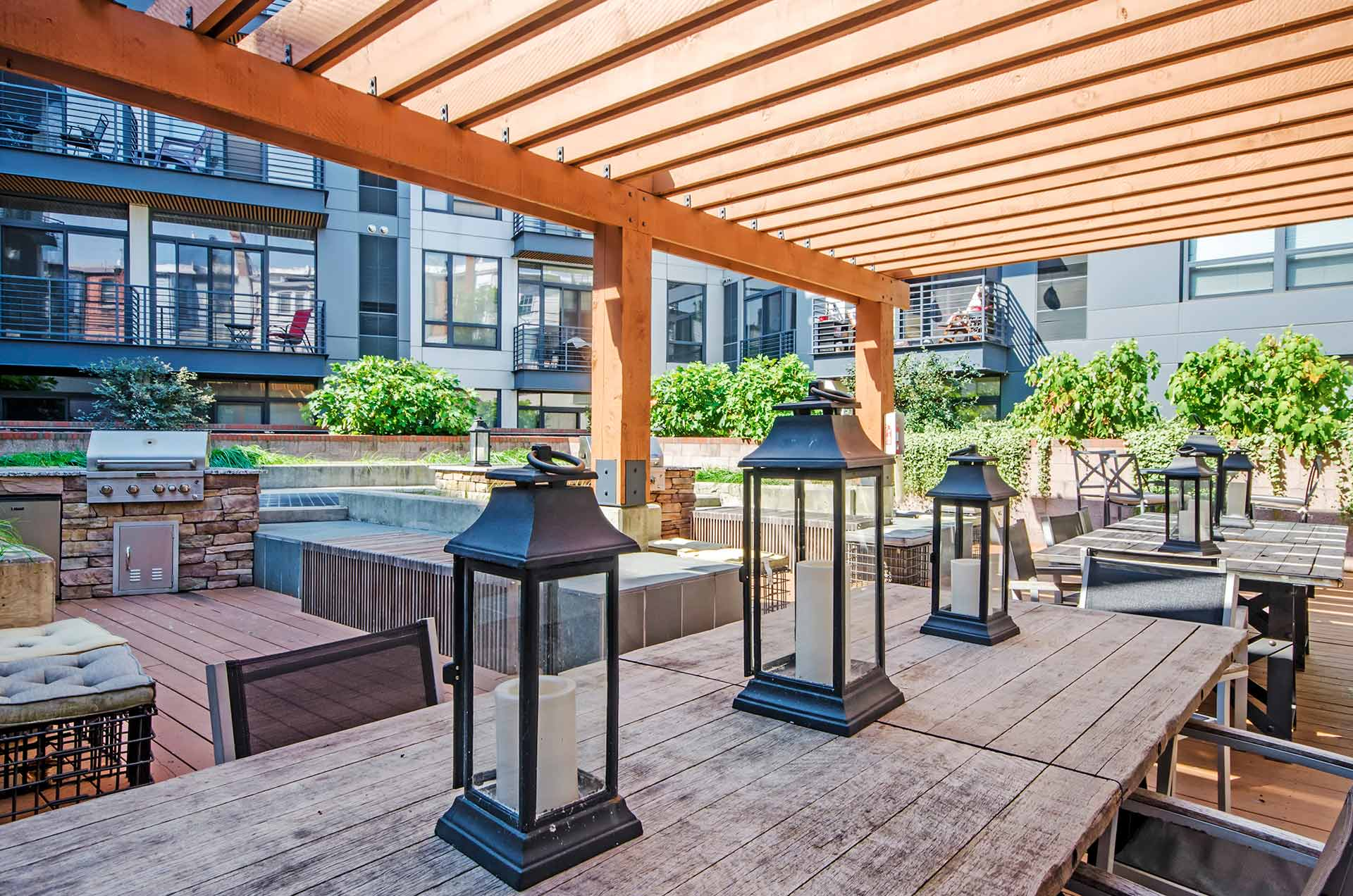 Interior courtyard closeup of communal tables with large lanterns, shaded trellis and grilling stations beyond