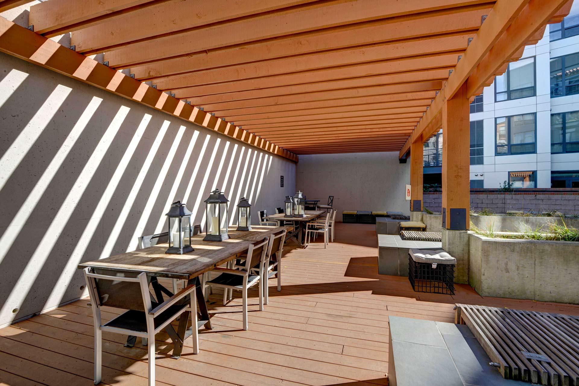 Interior courtyard closeup of café tables under the banded sunlight filtering through a trellis