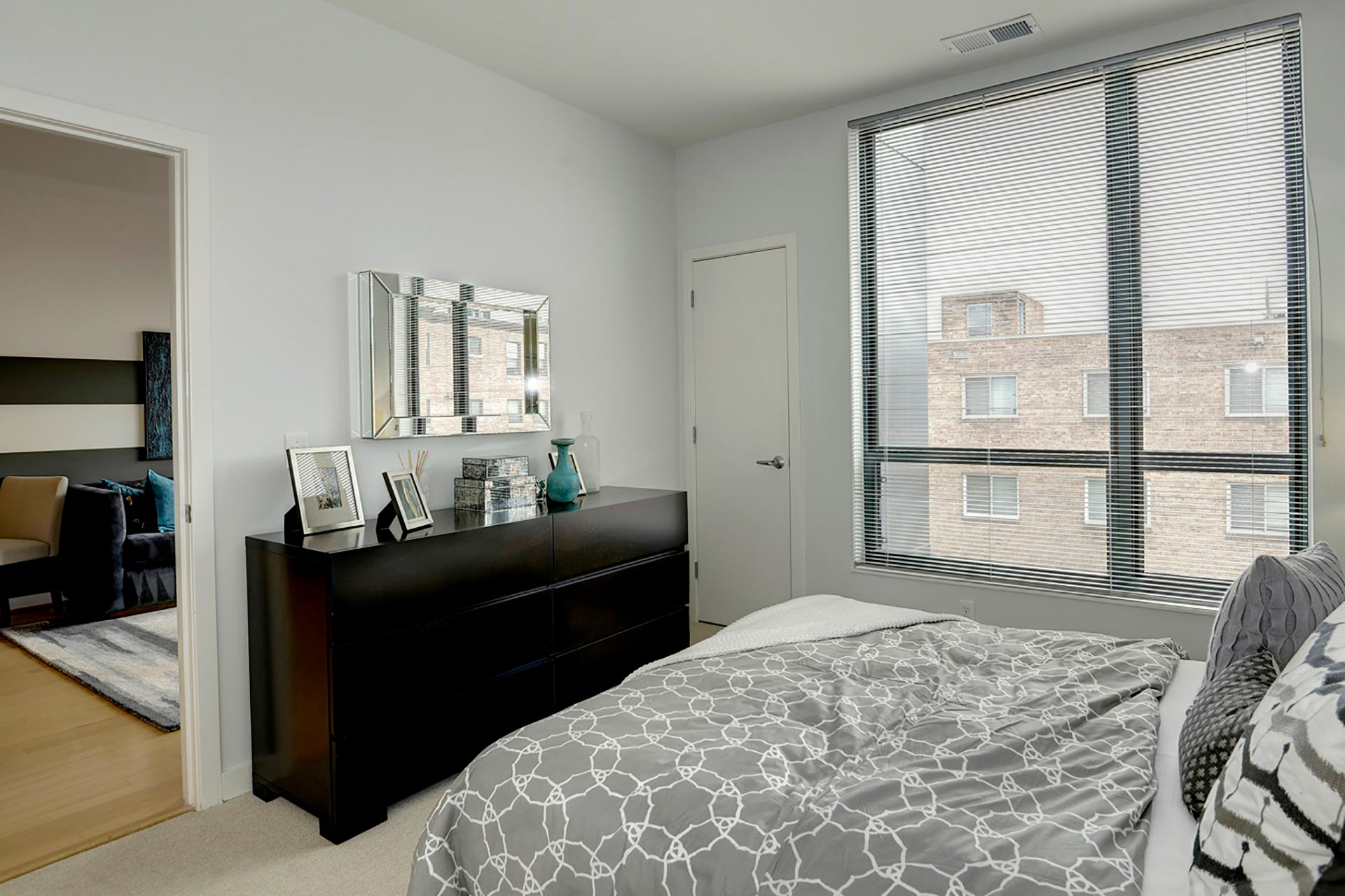Model unit bedroom with queen bed, dresser, and large window, with door open to the living room on the far left