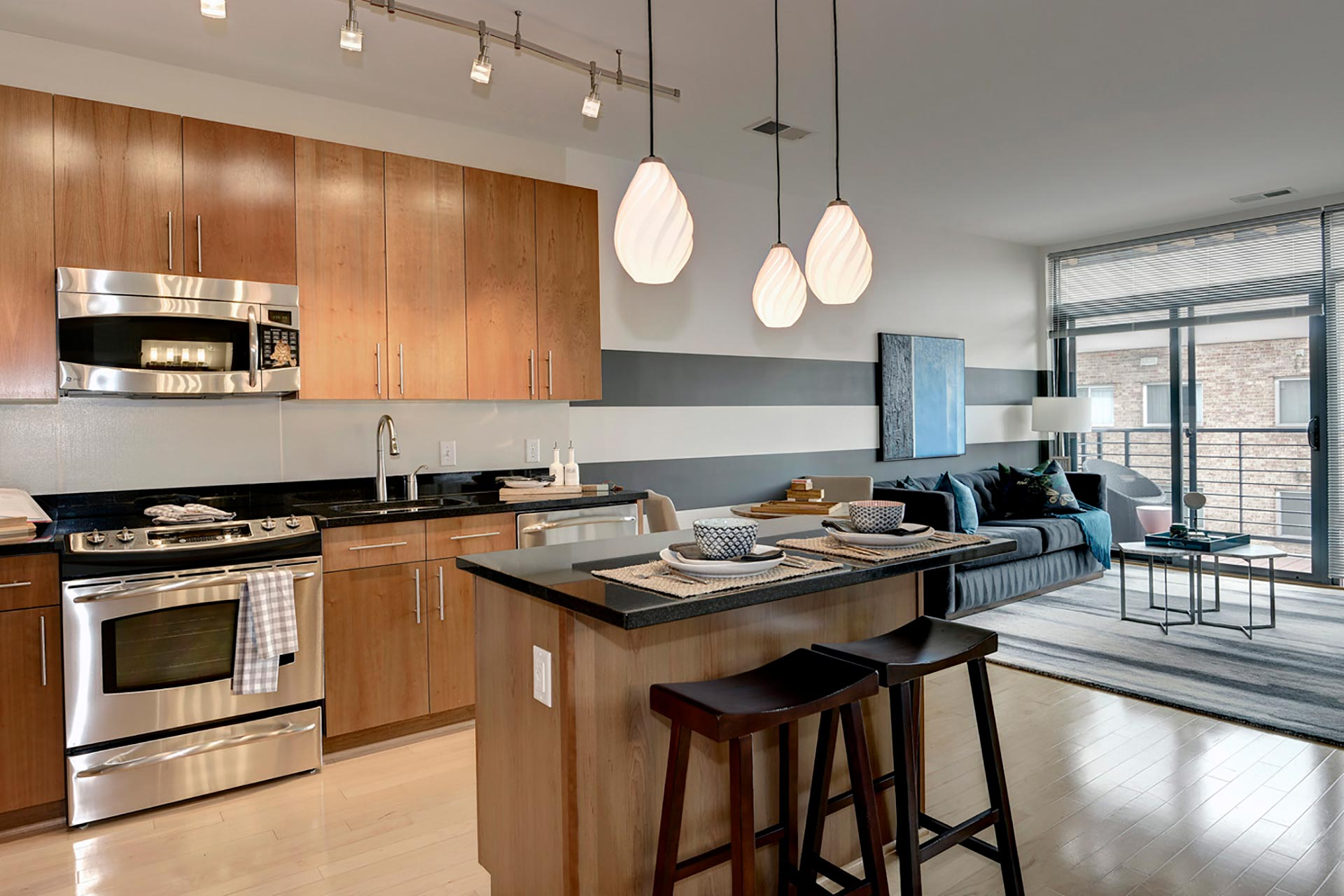 Angled view of model unit kitchen with stainless steel oven and microwave, bar island, and living room furniture beyond
