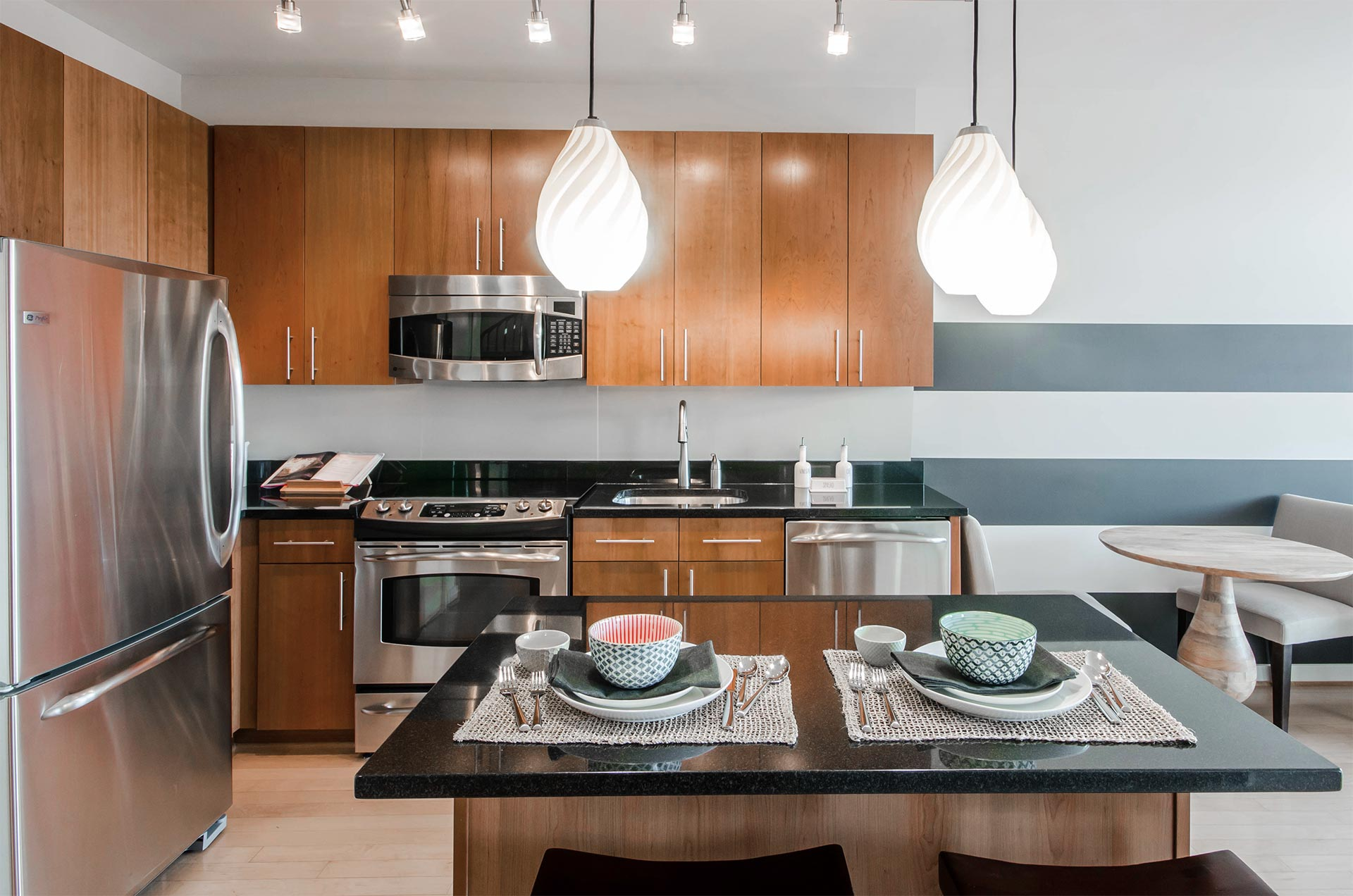 Straight on view of model unit kitchen with stainless steel fridge, oven, microwave, dishwasher and sink, and kitchen island