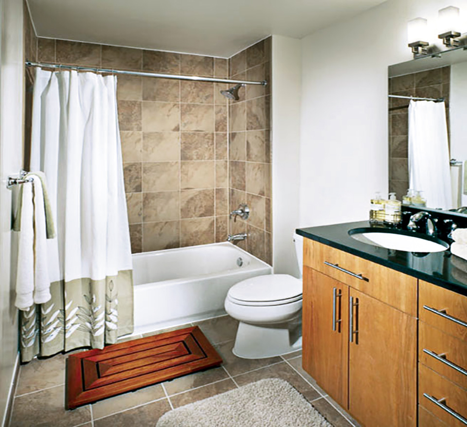 Model unit bathroom with double sink vanity, toiler, and tub shower with large format tiles
