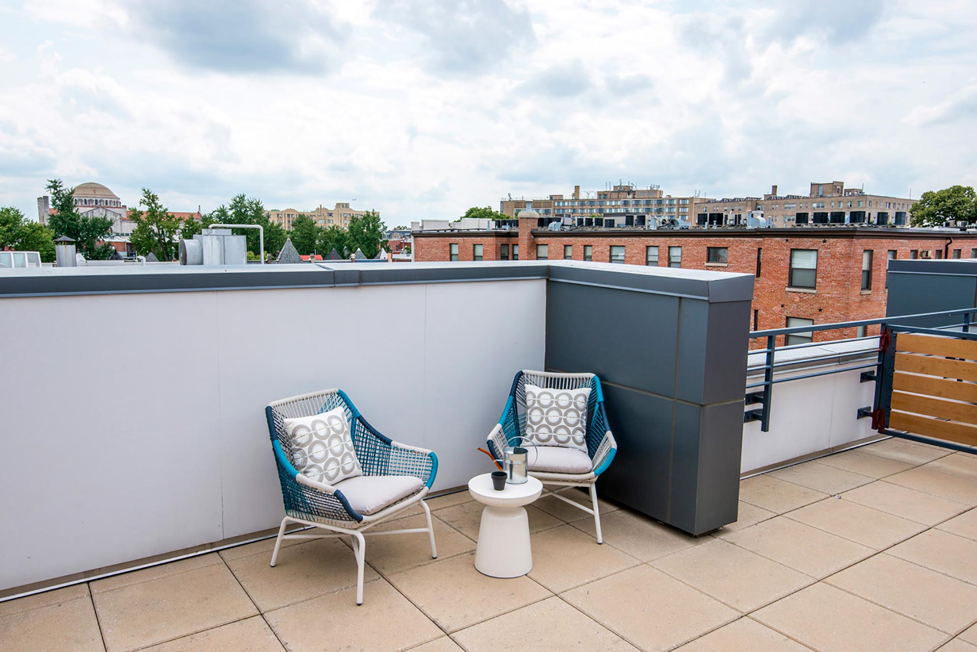 Closeup shot of outdoor furniture on private roof terrace with view of rooftops and trees beyond