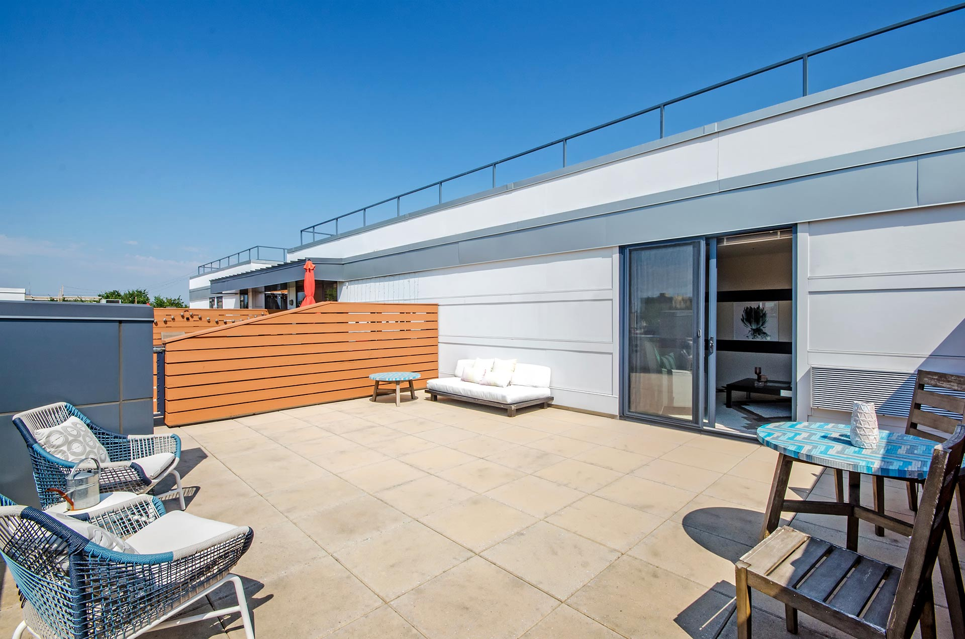 Expansive shot of outdoor furniture on private roof terrace with sliding doors open to apartment loft space inside
